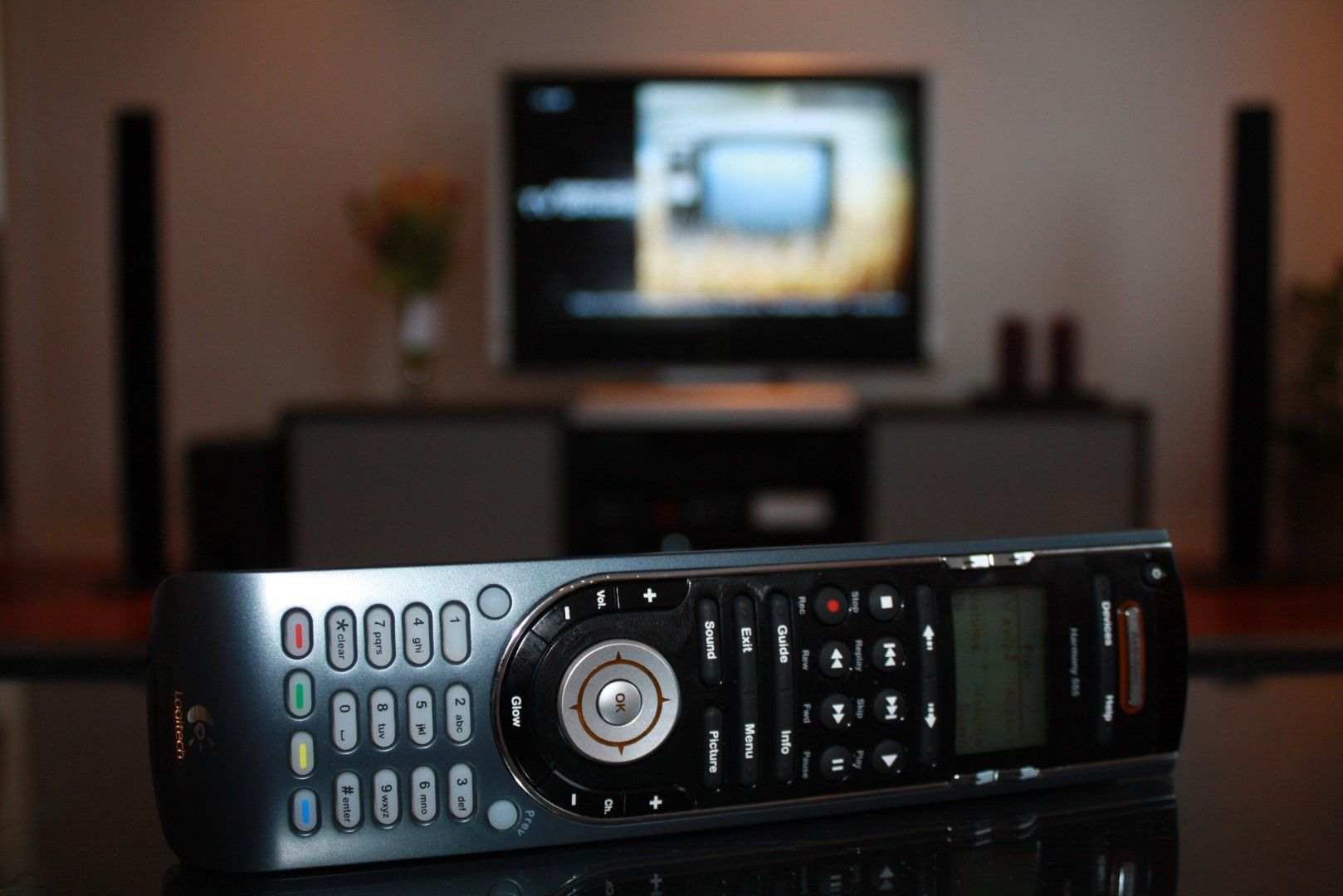 A Logitech Harmony 555 remote with an LCD screen, a D-pad, and a number of TV and media keys.