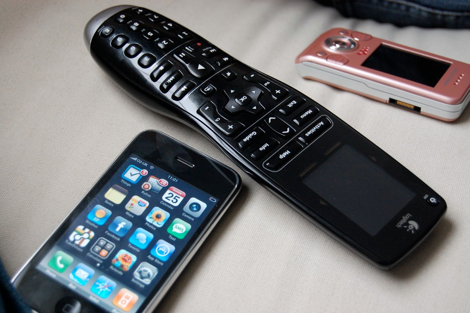 The Logitech Harmony One remote, alongside with a Sony Ericcsson slider phone and one of initial iPhone models.